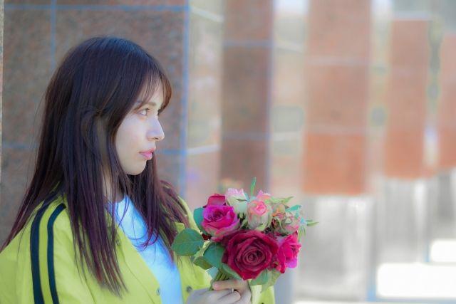 花束を持って立つ女性